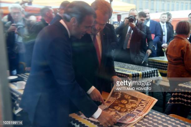 Finnish President Sauli Niinistö and French President Emmanuel Macron look at a Finnish newspaper reporting on Macron's visit as they take a walk on...