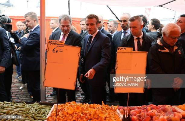 Finnish President Sauli Niinistö and French President Emmanuel Macron look at fruits and vegetables on display at a stand as they take a walk on a...