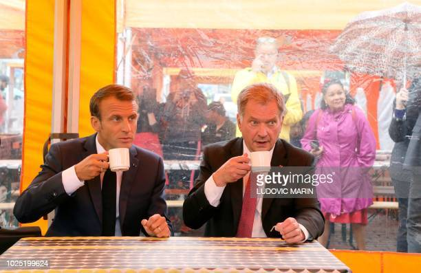 TOPSHOT Finnish President Sauli Niinistö and French President Emmanuel Macron take a drink on a street market outside of the Presidential Palace...