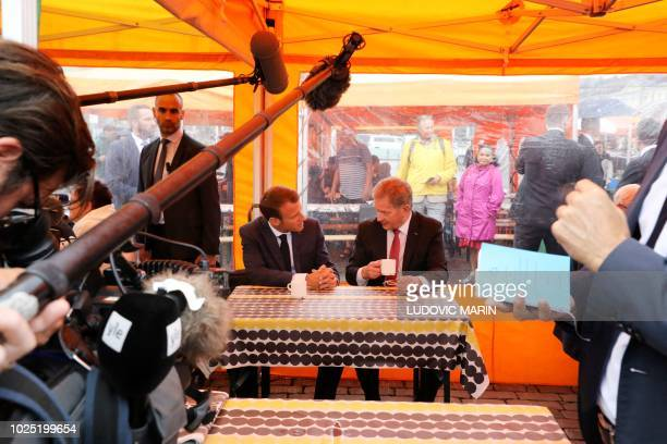 Finnish President Sauli Niinistö and French President Emmanuel Macron take a drink on a street market outside of the Presidential Palace after their...