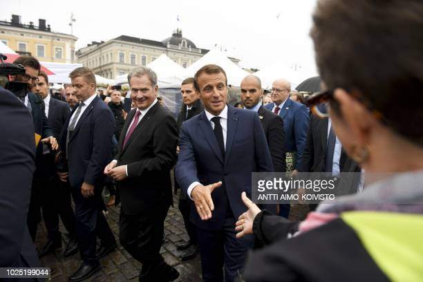 Finnish President Sauli Niinistö looks on as French President Emmanuel Macron shakes hands with a wellwisher during a walk outside of the...