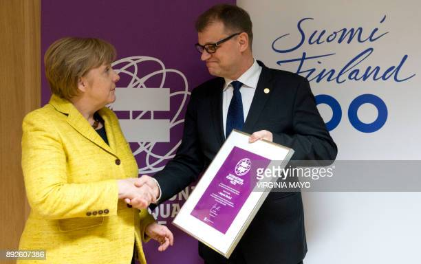 Finnish Prime Minister Juha Sipila presents German Chancellor Angela Merkel with the International Gender Equality Prize on the sidelines of an EU...