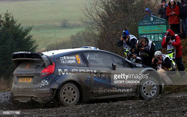 Finnish rally driver Mikko Hirvonen and his codriver Jarmo Lehtinen drive their Ford Fiesta RS WRC in the Alwen Forest special stage of the 2014...