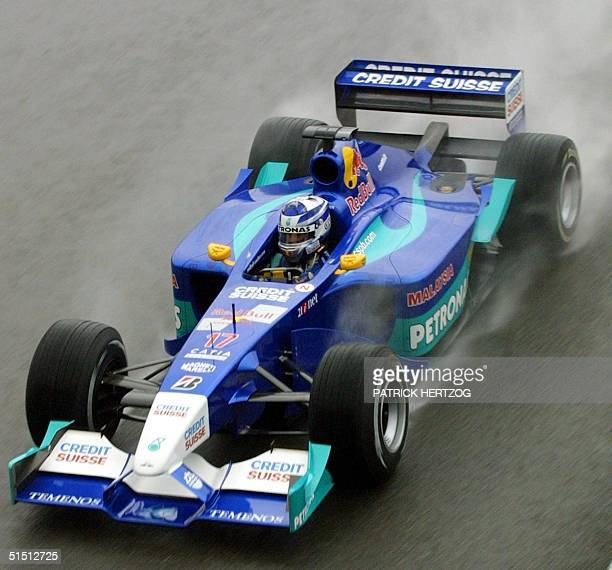 Finnish SauberPetronas driver Kimi Raikkonen steers his car as rain falls on the Silverstone racetrack 14 July 2001 during the second free practice...
