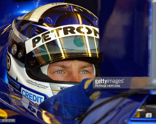 Finnish SauberPetronas driver Kimi Raikkonen watches TV screen in the pits of the Silverstone racetrack 13 July 2001 during the first free practice...
