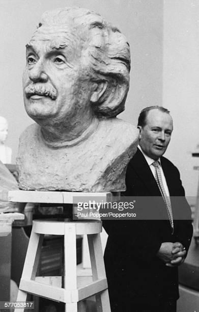 Finnish sculptor Kalervo Kallio pictured with a large bust of Albert Einstein, circa 1960.