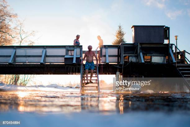 TOPSHOT Finns take a dip in an unfrozen hole of water after a sauna session on January 15 2017 in Vaasa as air temperature is 17°C and water is 1°C /...