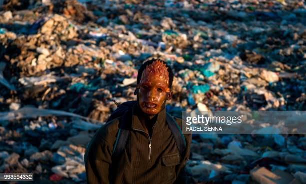 TOPSHOT Fintor a 22yearold migrant from Mali wearing a mask searches for objects and food in a garbage dump on July 05 2018 in Fnideq northern...