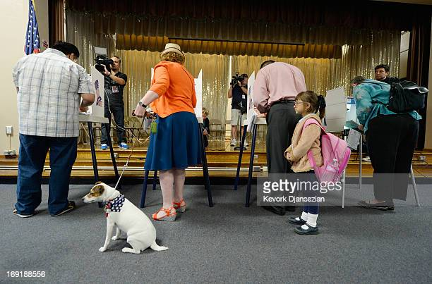 Fiona a Jack Russell Terrier waits for her owner Deborah Murphy as she votes and Maya Marquez waits for her father Mateo Marquez to vote at...