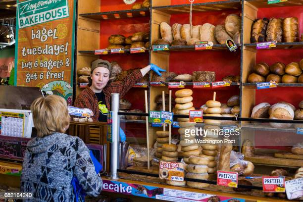 Fiona Carey of Ann Arbor, assists a customer in making a selection of bread from the baked goods counter at Zingerman's Delicatessen in the Kerrytown...