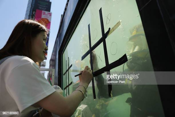 Fiona Huang plays tictactoe with a United States Navy diver in a tank during demonstrations and tours in Times Square as part of Fleet Week...