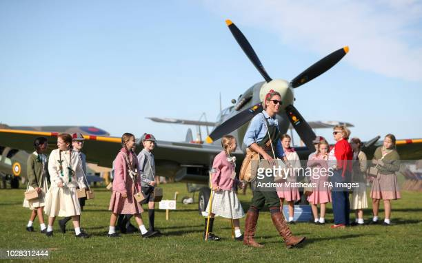 Fiona Lewis from Chichester leads school children from The March Church of England primary school past a Spitfire during day one of the Goodwood...