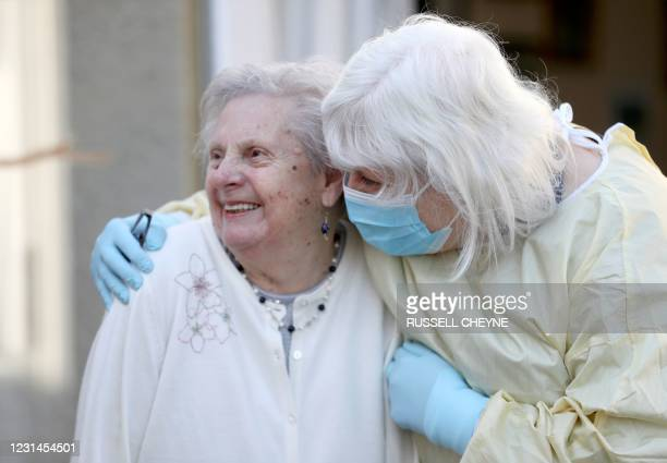 Fiona Scott , wearing PPE of a face mask and gloves, embraces her her mother Mary Cook as she visits her at her nursing home for the first time since...