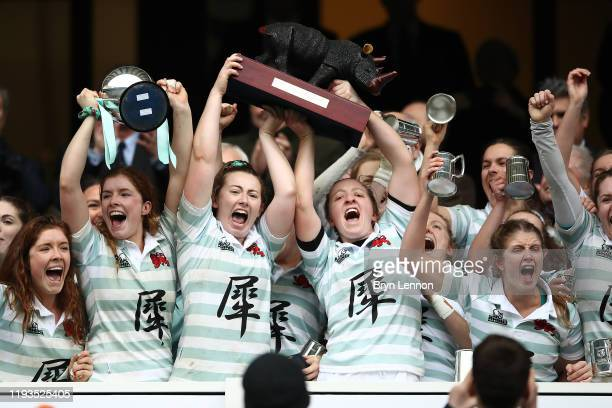 Fiona Shuttleworth, Bluebell Nicholls and Alice Elgar of Cambridge celebrate as they lift the trophy after winning the Women's Varsity Game between...