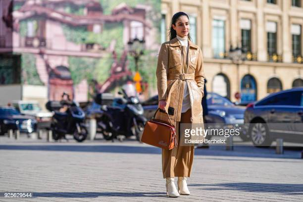Fiona Zanetti wears a beige leather coat flare brown pants a brown bag white shoes during Paris Fashion Week Womenswear Fall/Winter 2018/2019 on...