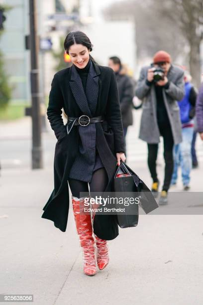 Fiona Zanetti wears a black coat red leather boots during Paris Fashion Week Womenswear Fall/Winter 2018/2019 on February 28 2018 in Paris France