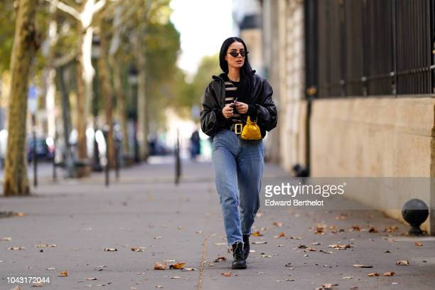 Fiona Zanetti wears a black leather jacket a striped top blue jeans a yellow bag outside Altuzarra during Paris Fashion Week Womenswear Spring/Summer...