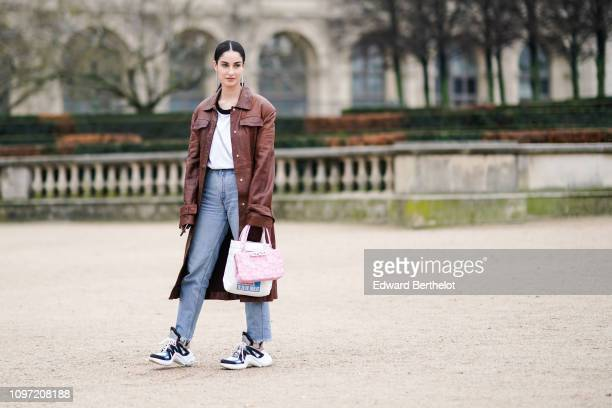 Fiona Zanetti wears a brown leather coat, a pink bag, sneakers, outside Kenzo, during Paris Fashion Week - Menswear F/W 2019-2020, on January 20,...