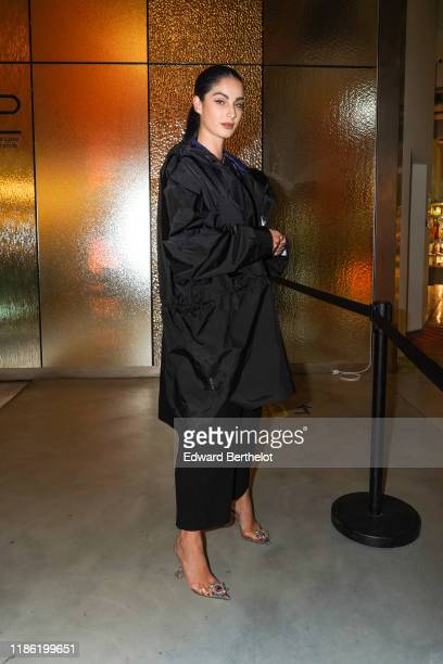 Fiona Zanetti wears a coat a bejewelled black top flare pants bejewelled pointy shoes during Moncler House Of Genius Paris Opening Event at Galeries...