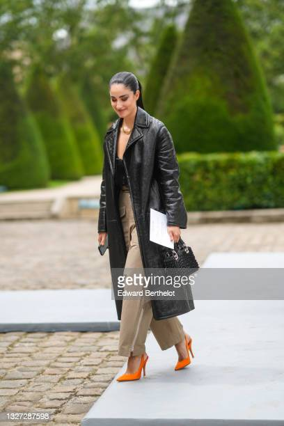 Fiona Zanetti wears a gold large chain CD pendant necklace from Dior, a black shiny leather long trench coat, a black mesh zipper crop-top, beige...