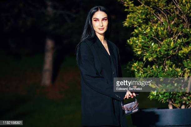 Fiona Zanetti wears a Jacquemus black mini bag with a chain a black oversized blazer jacket a white outfit outside Jacquemus during Paris Fashion...