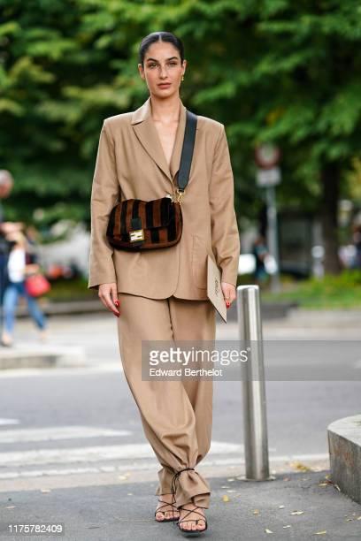 Fiona Zanetti wears a light brown blazer jacket, pants, a brown striped fluffy Fendi bag, outside the Fendi show during Milan Fashion Week...