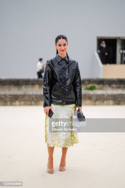 Fiona Zanetti wears gold and diamond earrings, a black shiny leather shirt coat, gold and silver rings, a yellow with rainbow reflect sequin midi...