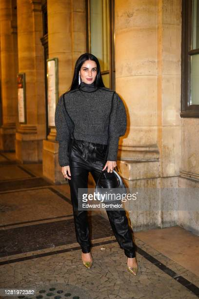 Fiona Zanetti wears long bejeweled earrings, a gray turtleneck oversized wool pullover with puff sleeves, black leather pants, a black leather...