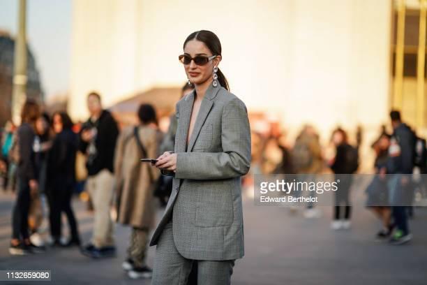 Fiona Zanetti wears sunglasses a earrings a purple shiny bag a gray blazer jacket suit flared pants outside Rochas during Paris Fashion Week...