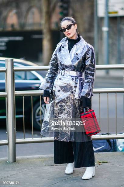 Fiona Zanetti wears sunglasses a red bag a plastic transparent trench coat during London Fashion Week February 2018 on February 17 2018 in London...