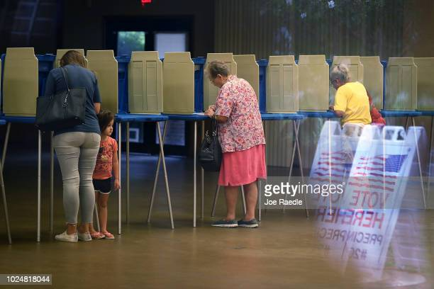 Fionna Beazzo stands with her mother Erin Beazzo as she fills out her primary day voting ballot next to Beverly Putzke at a polling station on August...