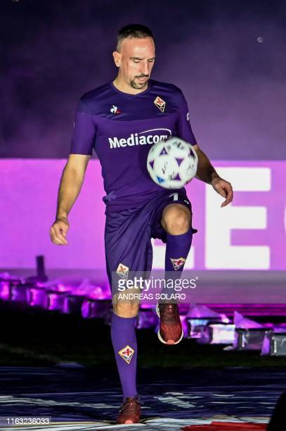 Fiorentina newly recruited players France's midfielder Franck Ribery plays with the ball during his presentation to supporters at the municipal...