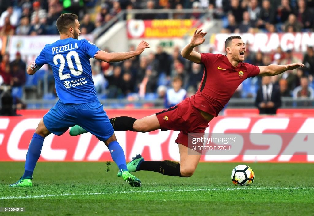 Fiorentina's Argentinian defender German Pezzella (L) fights for the ball with Roma's forward from Bosnia ed Erzegovina Edin Dzeko during the Italian Serie A football match AS Roma vs Fiorentina on April 7, 2018 at the Olympic stadium in Rome. /