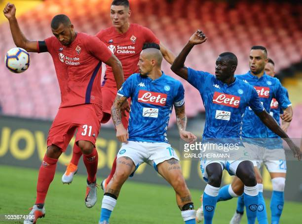 Fiorentina's Brazilian defender Vitor Hugo controls the ball next to Napoli's Slovak midfielder Marek Hamsik and Napoli's Senegalese defender Kalidou...