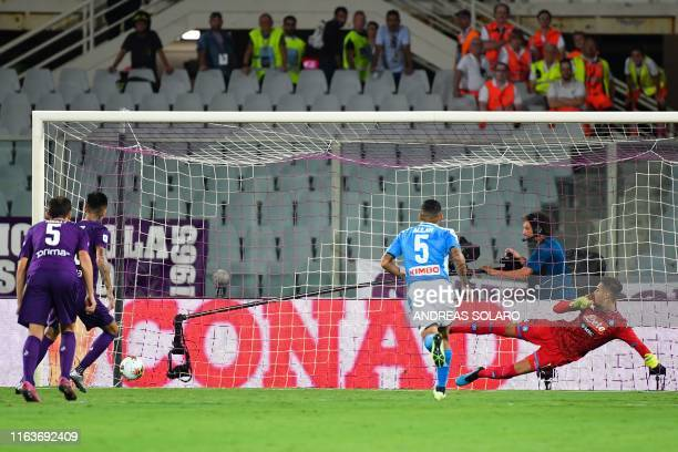 Fiorentina's Chilean midfielder Erick Pulgar scores a penalty past Napoli's Italian goalkeeper Alex Meret during the Italian Serie A football match...