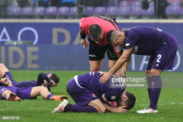 Fiorentina's midfielder and new captain Milan Badelj reacts as referee Fabrizio Pasqua and Fiorentina's defender Vincent Laurini comfort him on March...