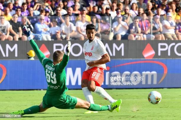 Fiorentina's Polish goalkeeper Bartlomiej Dragowski clears a ball under pressure from Juventus' German midfielder Sami Khedira during the Italian...