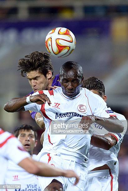 Fiorentina's Spanish defender Marcos Alonso Mendoza vies for the ball with Sevilla's Cameroonian midfielder Stephane M'Bia during the UEFA Europa...