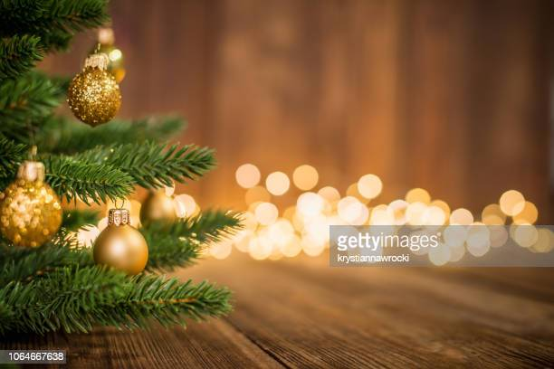 fir tree decorated with christmas balls on rustic wood and sparkles light backgorund - plano de fundo imagens e fotografias de stock