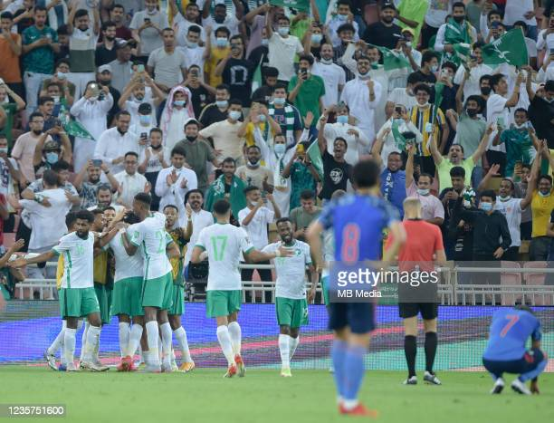 Firas Albirakan is swamped by his team-mates after scoring for Saudi Arabia against Japan during the 2022 FIFA World Cup Qualifier match at King...