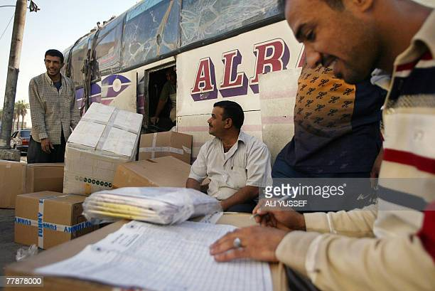 Firaz Abdul Amir a supervisor with a travel agency monitors the unloading of goods belonging to Iraqi refugees returning back home after they had...