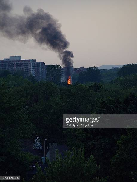 Fire Amidst Trees By Building Against Sky