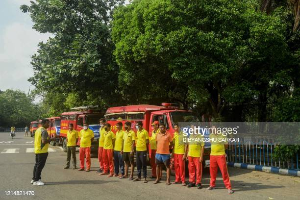 Fire and Disaster Service personnel of the neighbouring state of Odisha stand waiting to receive orders for the cleaning operation in the area...