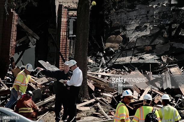 Fire and rescue crews and investigators are seen at the site of an overnight explosion and fire that destroyed an apartment building in the Flower...