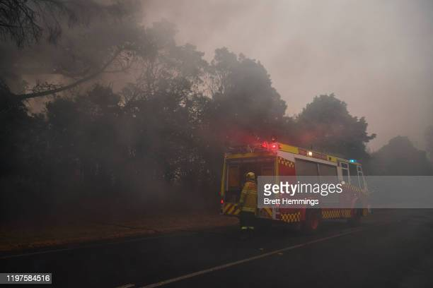 Fire and Rescue crews work to put out a smouldering tree on January 5, 2020 in Bundanoon, Australia. One person has died overnight in Batlow and four...