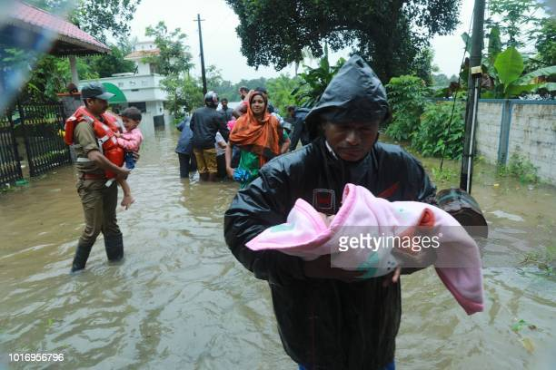 TOPSHOT Fire and Rescue personnel evacuate local residents in an inflatable boat from a flooded area at Muppathadam near Eloor in Kochi's Ernakulam...