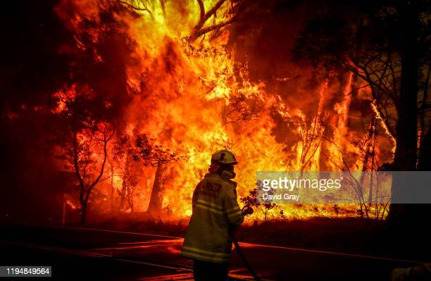Fire and Rescue personnel prepare to use a hose in an effort to extinguish a bushfire as it burns near homes on the outskirts of the town of Bilpin...