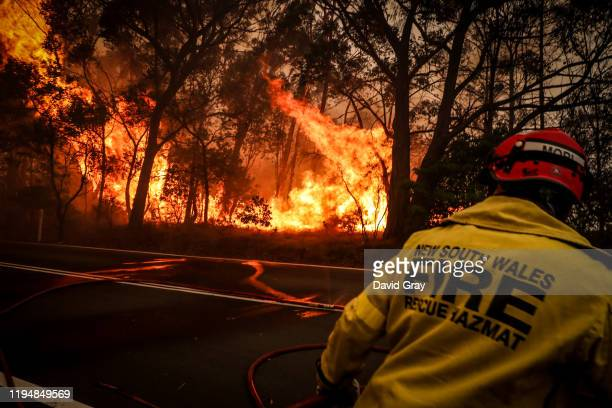Fire and Rescue personnel run from flames as a bushfire burns trees along a road near homes on the outskirts of the town of Bilpin on December 19...