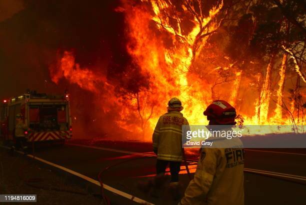 Fire and Rescue personnel run to move their truck as a bushfire burns next to a major road and homes on the outskirts of the town of Bilpin on...