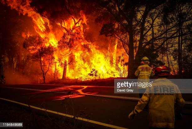 Fire and Rescue personnel watch a bushfire as it burns near homes on the outskirts of the town of Bilpin on December 19 2019 in Sydney Australia NSW...